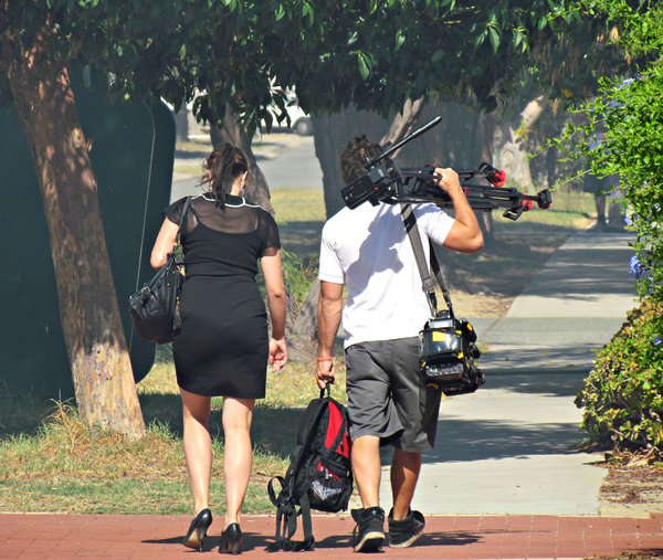capturing the news: TV news repoprter and camera man leaving scene of  house fire