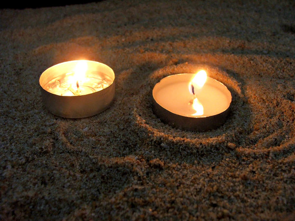 candles in the sand: lit devotional candles in sand