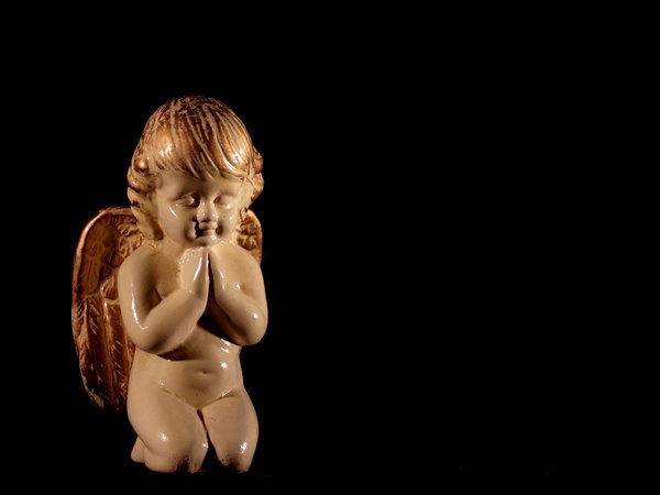 An angel praying: a small figurine of an angel praying. Black background.