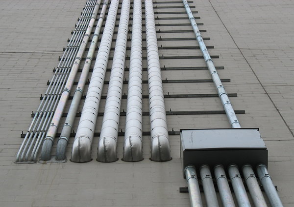 conduits: various electrical and cable conduits running up the side of a building.