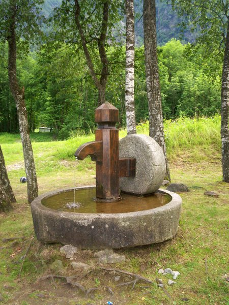 stone fountain: old fountain in a public place in the mountain, location Vallantrona, Lombardy, Italy