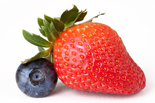 Berry Mix: Strawberry and blueberry close-up isolated on a white background.
