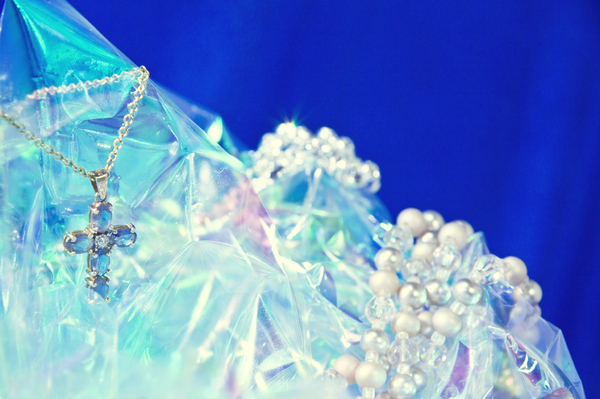 Jewelry Grouping: An iolite cross and pearls arranged on cellophane to give the appearance of ice.