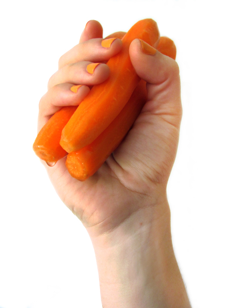 hand holding carrots: hand holding peeled carrots, orange nail polish, water drop, white backdrop