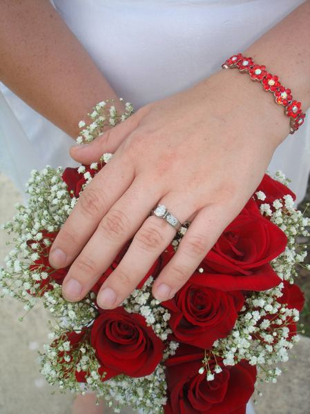 Wedding Ring and Flowers: Hand in front of flowers, instead of the normal holding the flowers, displaying the wedding ring