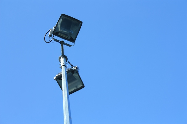 Floodlights: Floodlights at a sports venue against a clear blue sky