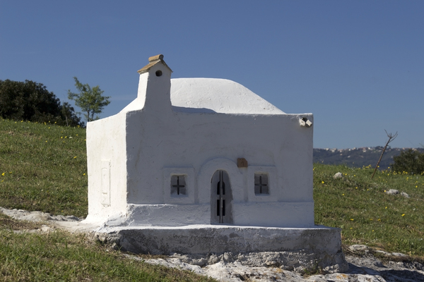 Gravestone like a tiny house: A gravestone resembling a tiny house in a rural churchyard in Puglia, southern Italy.