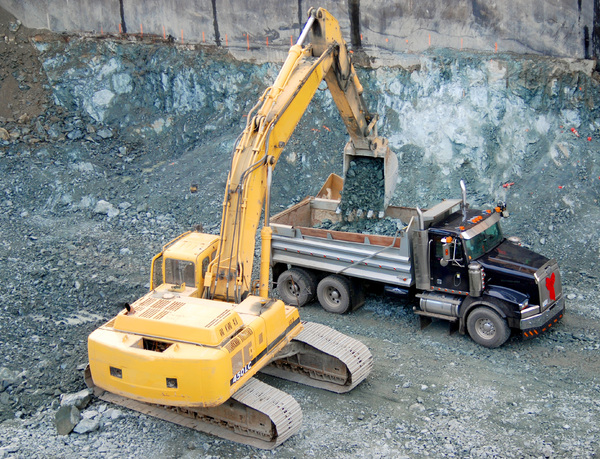 Excavation: Excavator in a construction pit dropping rocks into a dump truck.