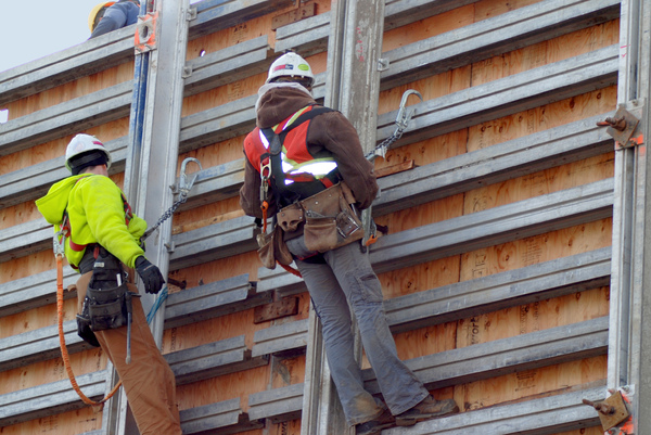 Construction Workers: Two construction workers harnessed to a wall.