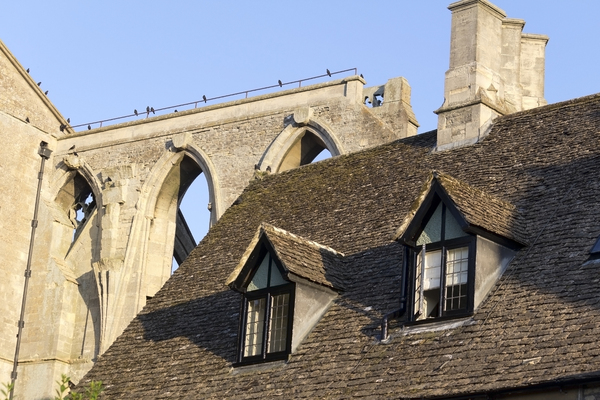 Elements of old architecture: Dormer windows of an ancient house with the remains of an abbey in the background in evening sunlight in Wiltshire, England.