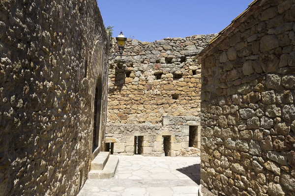 Ancient courtyard: A courtyard and defensive wall in an ancient village in Catalunya, Spain.