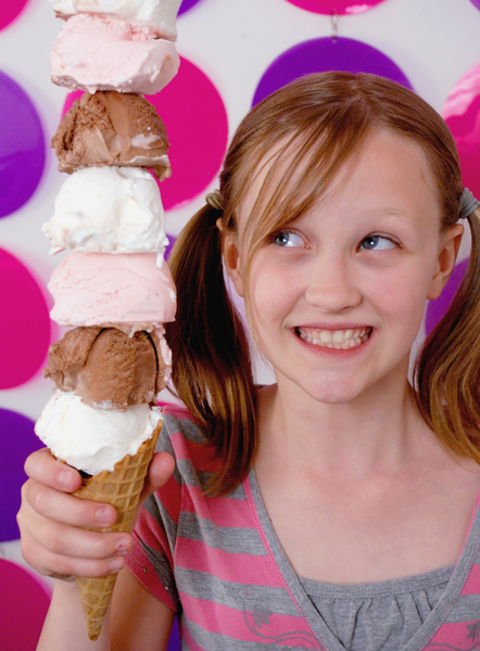 X-tra Scoops: Excited girl holding a ridiculously large ice cream cone.