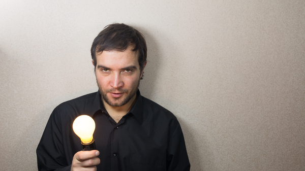 Young Man Having an Idea.: Young Man Having an Idea. Man with a light bulb.
