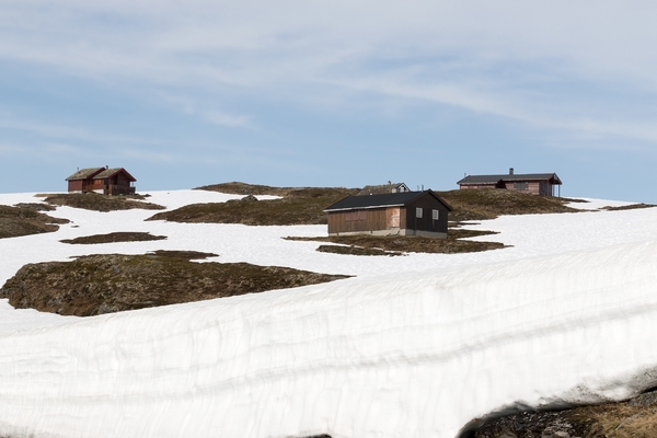 Snow houses: Houses on a snowy mountain on a high plateau in Norway in July.