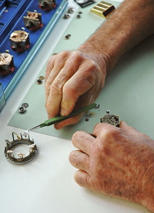 Working with his hands: A clockmaker, or horologist, working with a wristwatch's inners.NB: Credit to read