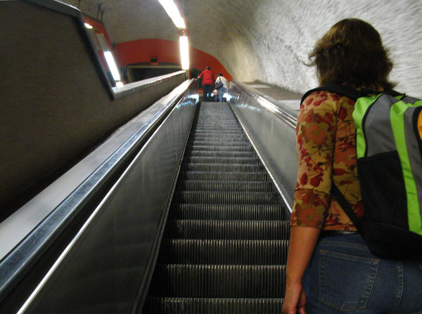 Subway mechanical stairs: Woman with backpack at bottom of subway mechanical stairs going up