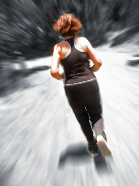 Woman Jogging Blur: Young woman jogging, seen from behind, scenery blurred to denote speed