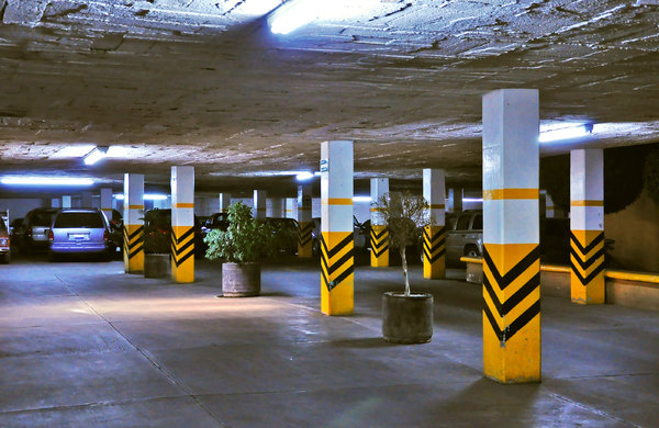 Parking lot: Shot of an underground parking lot in dim lights, cars in the background
