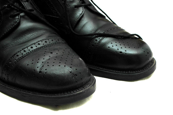 shoes: Pair of black shoes. One polished shoe and one unpolished shoe.