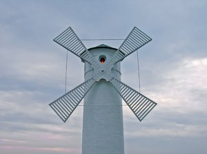 fixed beacon windmill: a fixed beacon windmill which is in fact a lighthouse at the pier of Świnoujście, Poland