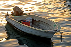 Weathered Boat: A weathered motorboat at sunset