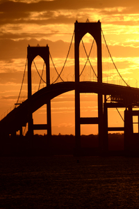 Newport Bridge Sunset: The Newport Bridge silhouetted by a bright yellow sunset
