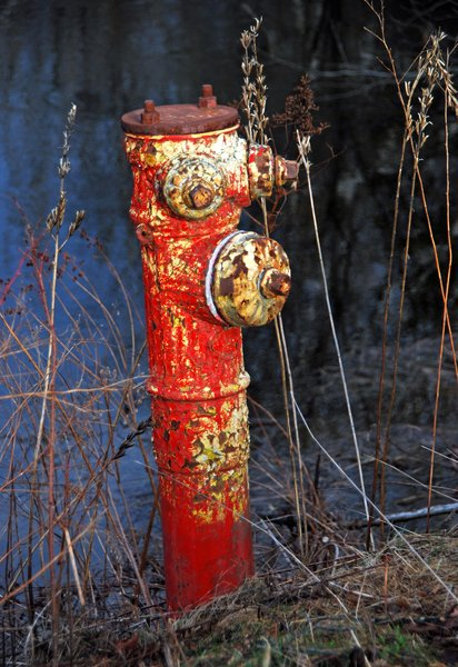 Old Red Hydrant: An old fire hydrant on route 1 entering Searsport Maine. The various nozzles and bolts seem to give it the appearance of having a face.