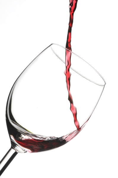 Glass of red wine: just start to poor in a glass with red finest wine