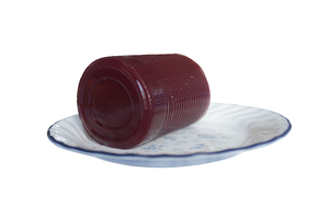 Cranberry Sauce: Cranberry Sauce as it comes out of a can on plate with a white background.
