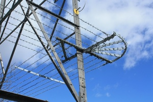 Barbed wire: Barbed wire stopping people climbing an electricity pylon