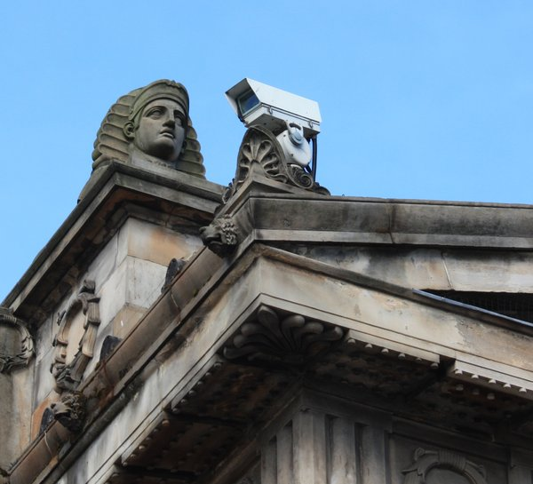 Who is watching over you?: Statue and CCTV watching over a city