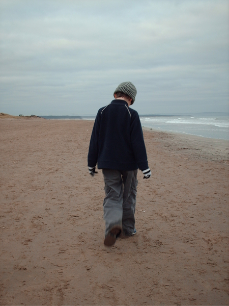 Boy on beach: Boy walking on a quiet beach