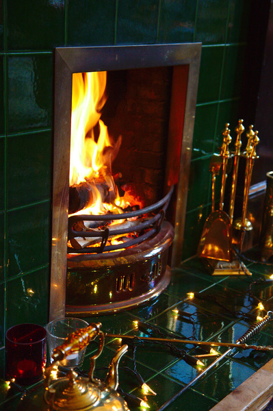 Christmas Fire: Fireplace with log fire and some Christmas lights