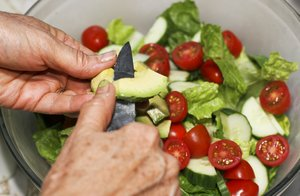 Dinner Salad: Cutting up the avocado on top of the salad.