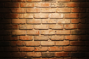 Spotlight on Brick Wall: Bare brick wall illuminated from top by bright single light source