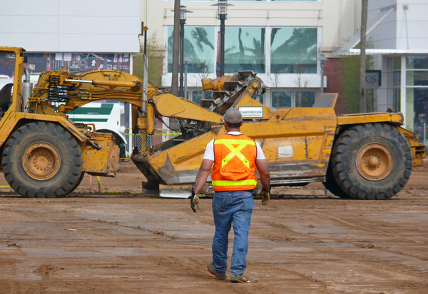 Back to work: A burley heavy equipment operator walks back to his machine.
