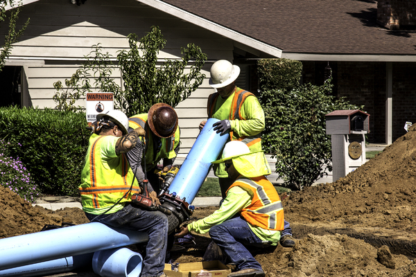 Work Crew Fitting Pipe: Construction crew install a pipe to water main elbow