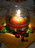 Candle & candy: A lit candle in a water bowl, surrounded by multicoloured candy.