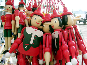Red dolls: Wooden dolls hanging up on a market stall in Venice.