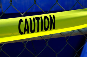Caution tape: Caution/warning tape on a chain link fence.