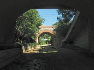 road under bridges: path under the railway and the road. S.Vincenzo, Tuscany, Italy.