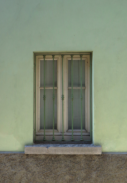 green window: window with bars on a green wall