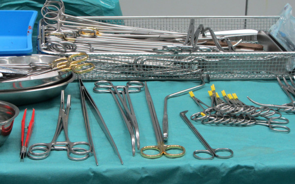 Surgical instruments: Table with surgical instruments like scissors, serrefines, couter and tweezers in an operation room