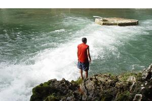 Inviting water: A young man contemplates the fresh and white water of a river.