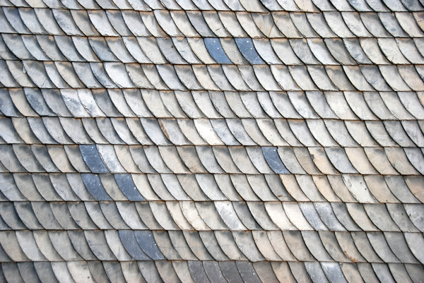 Slate texture: Fine-grained, foliated, homogeneous, metamorphic rock derived from an original shale-type sedimentary rock composed of clay or volcanic ash through low grade regional metamorphism. Here used as cladding of a house meant to shed water and protect from the