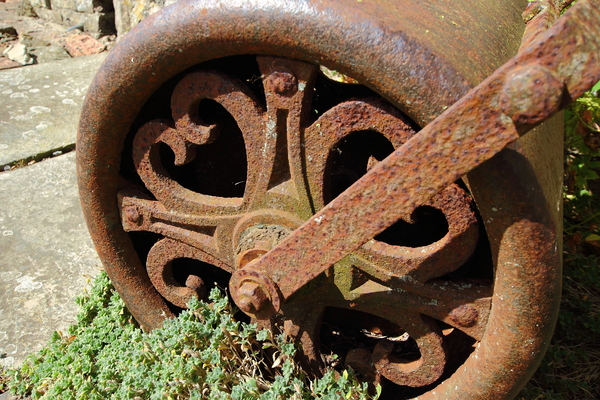 Garden roller: A rusty garden roller against an old stone wall