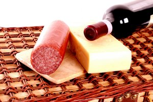 Wine, cheese and sausage on pi: A bottle of wine, some cheese and sausage on top on a picnic basket. Isolated with white background.