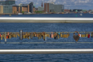 Padlocks for love - HDR: Padlocks locked onto a bridge crossing Copenhagen Harbour, Denmark. The padlocks are symbols of love and the couples have written their name and sometime a date on the locks. The image is HDR.
