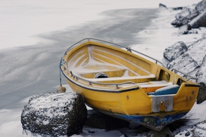Stranded on rocky winter beach: Dinghy, small rowing boat, stranded on rocks at coastline with ice and snow.