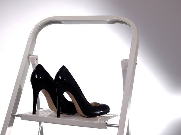 High heels on a step ladder: A pair of black high heel shoes on a step ladder.